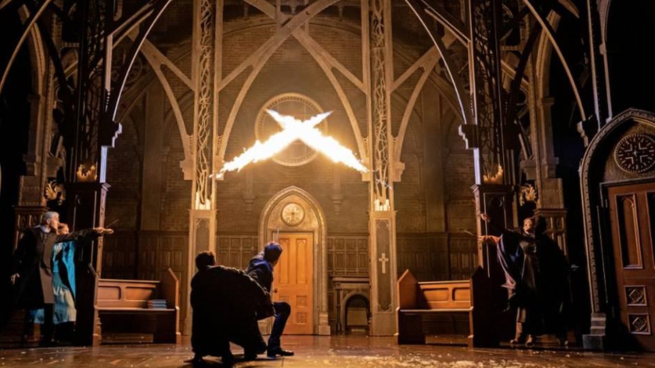 Zwei Zauberer knien mit gezückten Zauberstäben vor zwei Säulen, aus denen Flammen schlagen. Im Hintergrund eine Holztür