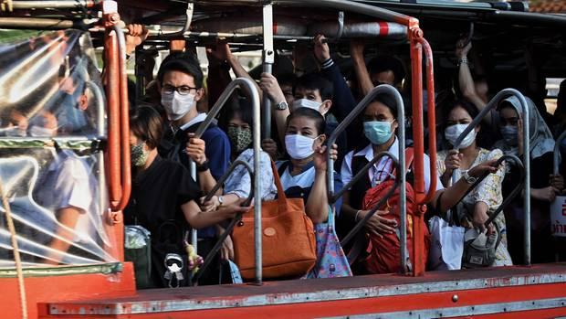 Menschen in Thailand tragen Mundschutz um sich vor dem Coronavirus zu schützen