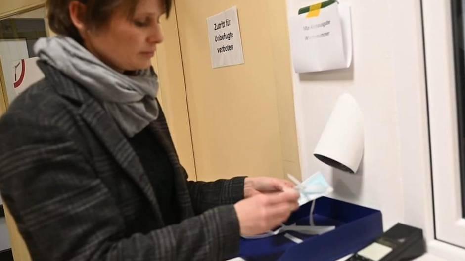 Eine Frau mit kurzen, braunen Haaren steht vor einem Fenster und füllt ein Formular aus