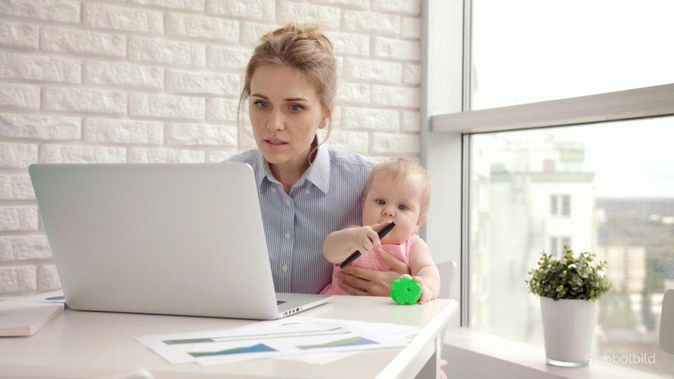 Eine Frau sitzt vor einem Laptop und hält gleichzeitig ein Baby im Arm