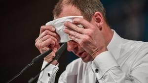 Friedrich Merz sitzt schwitzend vor zwei Mikrofonen und wischt sich mit einem weißen Tuch die Stirn