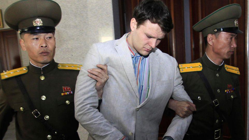 Der amerikanische Studenten Otto Warmbier wird von zwei nordkoreanischen Polizisten zum Obersten Gerichtshof begleitet.