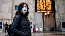 Eine Passantin mit Atemschutz steht im Hauptbahnhof von Mailand
