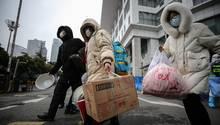 Patienten, die von einer Infektion mit dem neuartigen Coronavirus genesen sein sollen, verlassen eine improvisierte Krankenstation im chinesischen Wuhan.