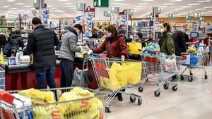 Kunden stehen im Kassenbereich eines Supermarktes