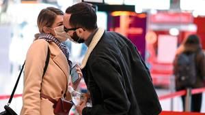 Ein Paar deutet Mundschutz tragend einen Kuss an