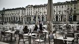 Zwei mutige Gäste auf einer verlassenen Caféterrasseauf der Piazza Vittorio in Turin.Bars und Restaurants können vorerst von 6bis 18Uhr geöffnet bleiben, sofern ein Sicherheitsabstand von mindestens einem Meter zwischen den Gästen eingehalten wird.