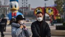 Erste Anzeichen für eine Normalisierung des Lebens? Eine chinesische Familie trägt Schutzmasken beim Besuch von Disneytown in Shanghai am Dienstag.