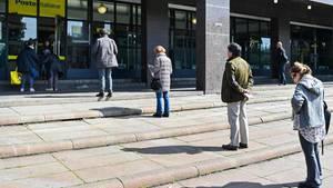 Menschen stehen vor einer Post-Filiale in Rom Schlange