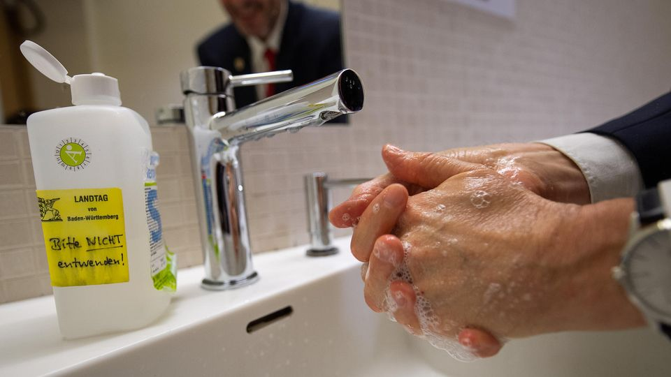 Ein Mann steht an einem Waschbecken und wäscht sich gründlich die Hände