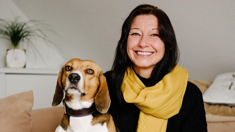 Beagle Toffee und seine dunkelhaarige Besitzerin. Sie trägt einen gelben Schal