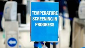 """Ein Schild mit der Aufschrift """"Temperature Screening in Progress"""" weist auf eine Einrichtung zur Messung der Körpertemperatur hin."""