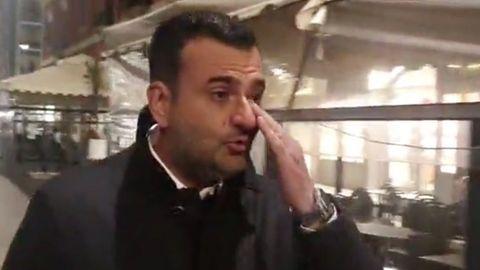 Ein eleganz gekleideter Mann mit schwarzen Locken wischt sich mit Links eine Träne aus dem Auge. Im Hintergrund ein Restaurant