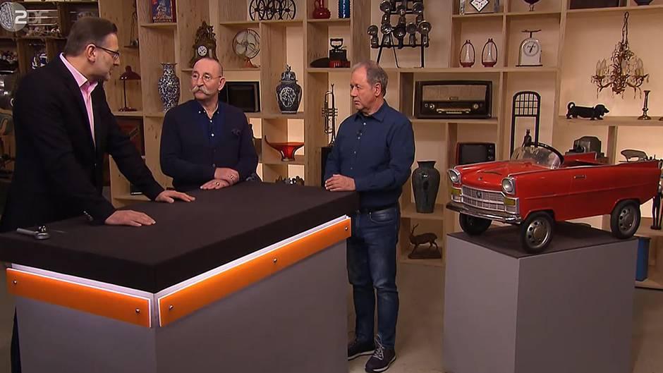 """Drei Männer und das Spielzeugauto: """"Bares für Rares""""-Experte Detlev Kümmel undModerator Horst Lichter sprechen über das Objekt vonHubert Büttgenbach (v.l.)"""