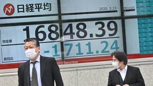 Eine Anzeigetafel in Tokio zeigt den fallenden Kurs des Nikkei-Index