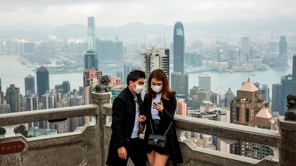 Ein Pärchen mit Mundschutz steht vor der Skyline Hongkongs