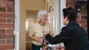 Ein junger Mann liefert Einkäufe an eine ältere Dame