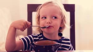 Ein kleines Mädchen isst Suppe