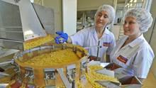 Zwei Frauen in weißer Hygienekleidung stehen an einer Verpackungsmaschine, in der Pasta in unterschiedliche Trichter fällt