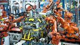 Zahlreiche Roboter arbeiten am Montageband an einem Auto