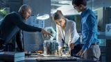 Eine Gruppe von Forschern arbeitet an einem Bauteil