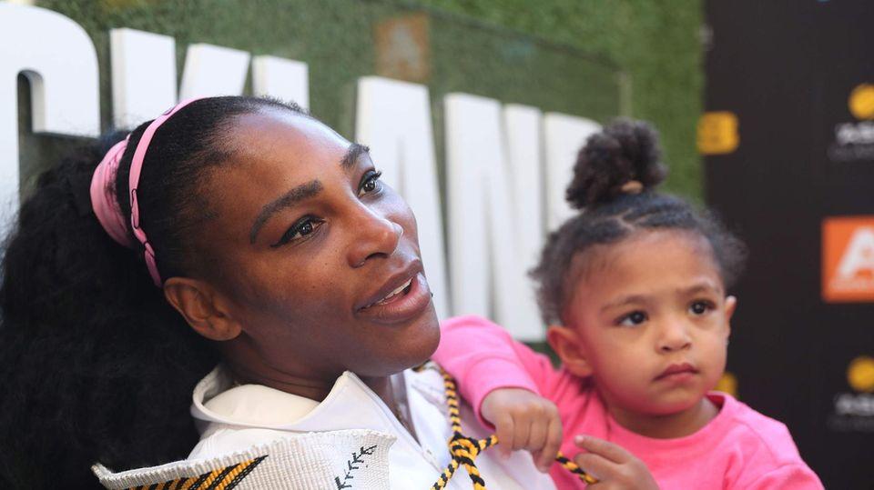 Serena Williams gibt ein Interview, während sie ihre kleine Tochter auf dem linken Arm trägt