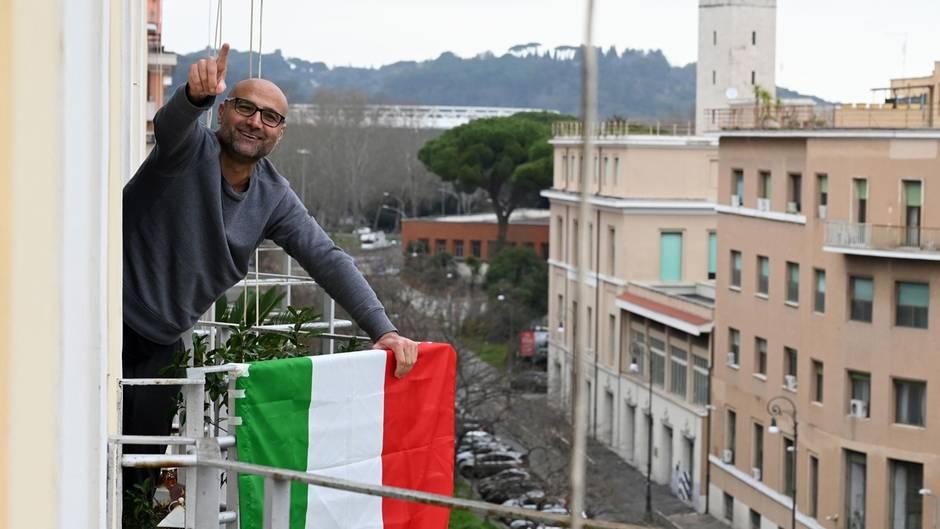 """Italien in Zeiten von Coronavirus: Ein Mann singt """"Un applauso per l'Italia"""" auf seinem Balkon in Rom"""
