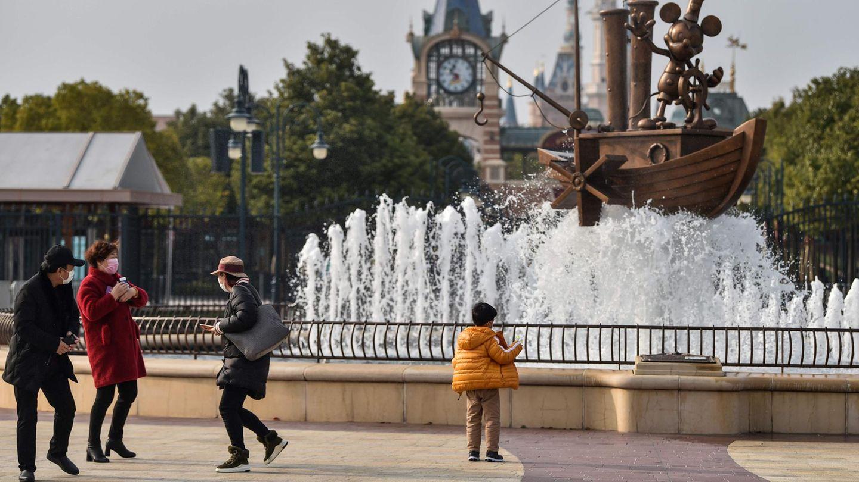 Besucher mit Mundschutz betrachten einen Springbrunnen