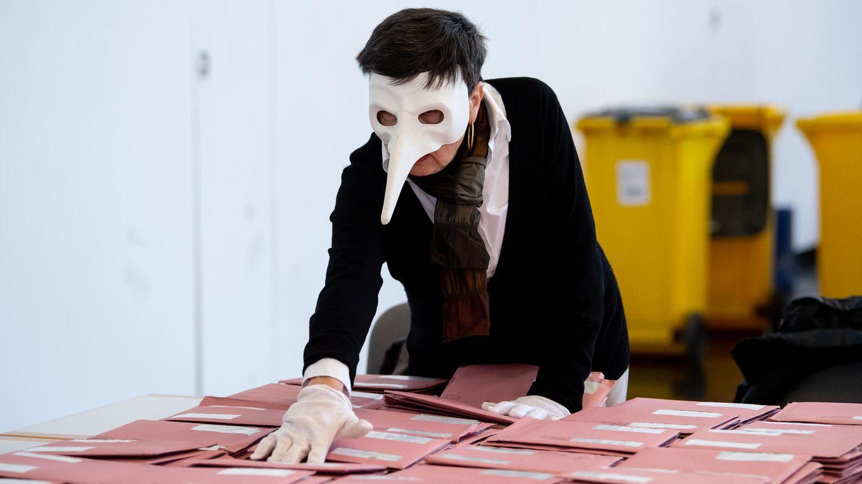 Eine Wahlhelferin mit einer Pestmaske bereitet in München die Auszählung der Briefwahl vor