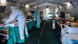 Medizinsches Personal in Schutzanzügen bereitet eine provisorische Triage-Stelle vor dem Krankenhaus in Brescia vor.