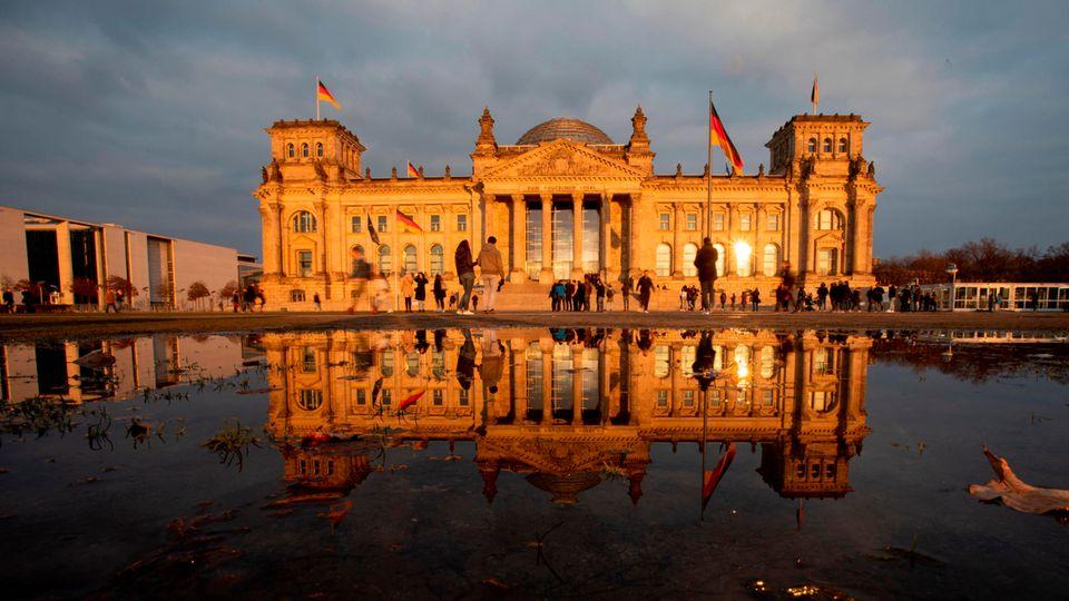 Das Reichstagsgebäude in Berlin liegt vor einem grauen Himmel in der Abendsonne und spiegelt sich im Wasserbecken davor