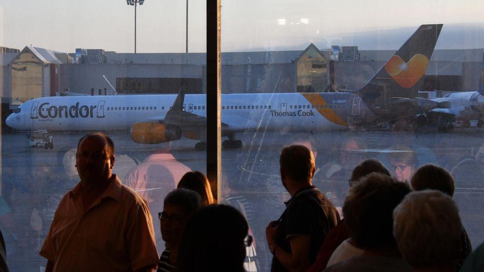 Passagiere schauen auf das Rollfeld, wo ein Flugzeug steht