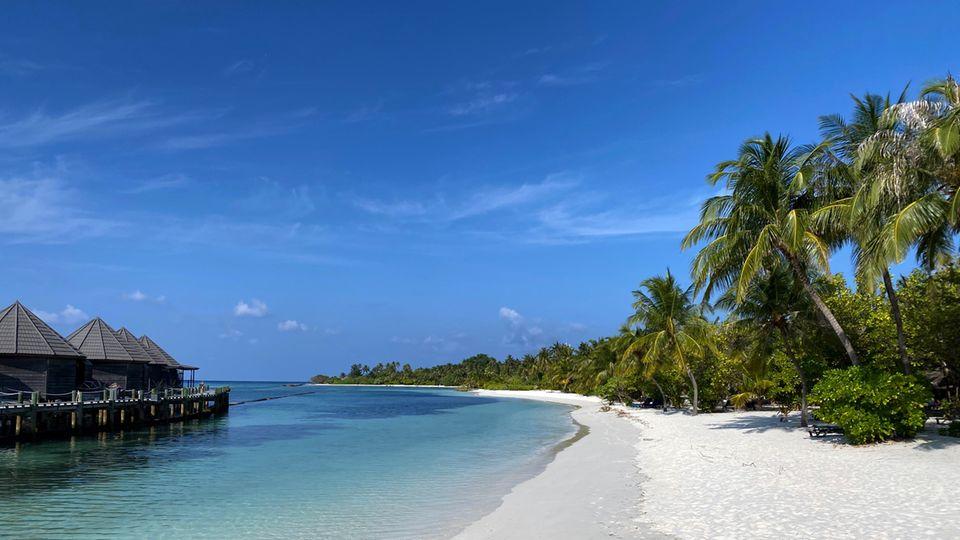 Blick einen weißen Strand hinunter. Rechts stehen Palmen, links stehen Hütten auf Pfählen im blauen Wasser