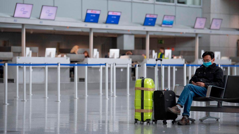 Mit einer Gesichtsmaske schützt sich dieser Mann in der Abflughalle des Terminals am Frankfurter Flughafen