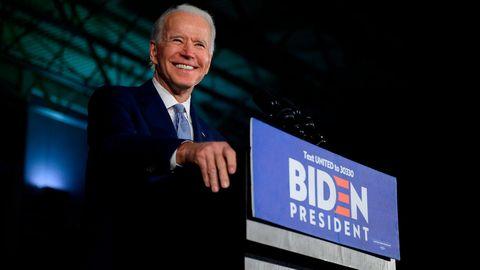 Joe Biden spricht von einem Podium und lächelt