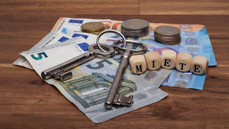 """Geld auf dem Tisch mit zwei Schlüsseln und Würfel mit der Aufschrift """"Miete"""""""