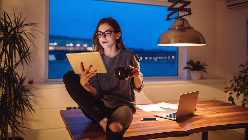 Eine junge Frau sitzt im Home Office und schaut auf ihr iPad