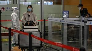 Eine Frau kommt amShanghai Pudong International Airport an und wird von Sicherheitskräften auf Anzeichen für Corona gecheckt