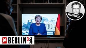 Zwei Menschen sehen die Rede von Bundeskanzlerin Angela Merkel (CDU)