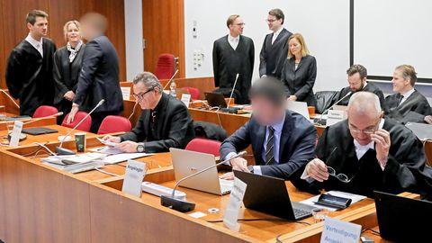 Die Angeklagten (3.v.l, und 2.v.r) stehen bzw. sitzen zusammen mit ihren Verteidigern im Landgericht auf der Anklagebank