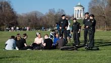 Junge Menschen picknicken im Park, Polizisten reden mit ihnen