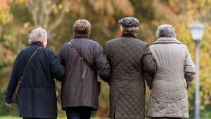 Vier ältere Menschen laufen Arm in Arm