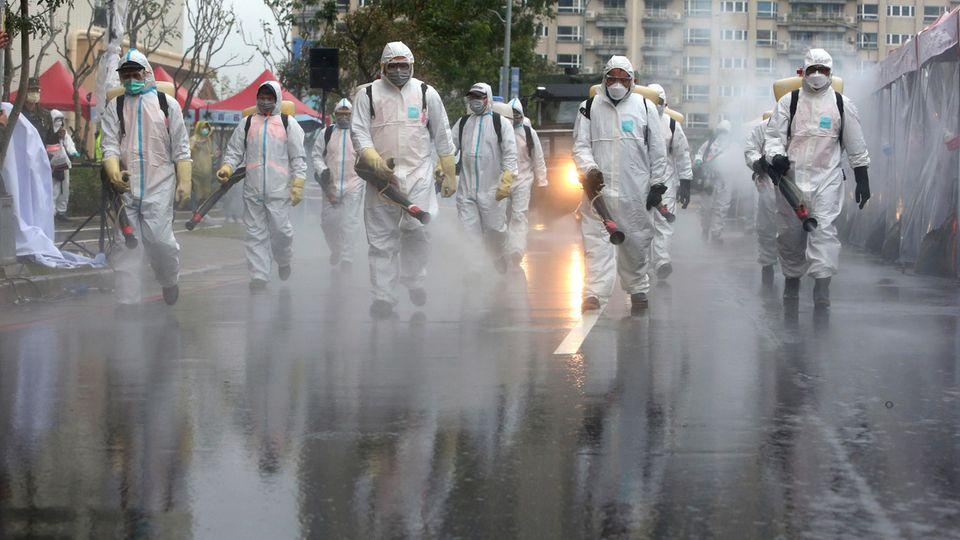 Soldaten der taiwanesischen Armee in Schutzanzügen sprühen während einer Übung Desinfektionsmittel auf eine Straße