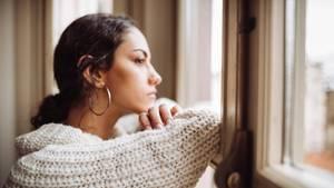 Eine Frau guckt nachdenklich aus dem Fenster