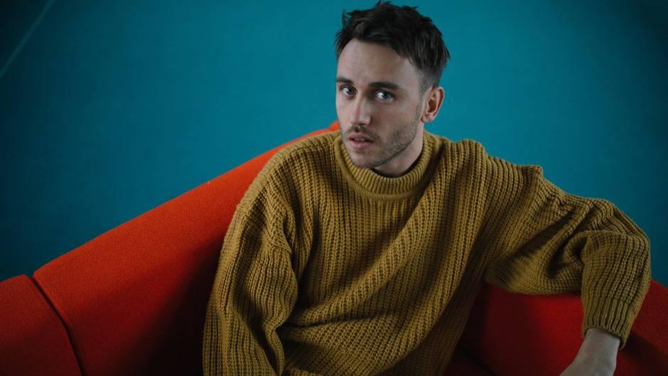 Clueso im gelben Strickpullover auf einem roten Sessel mit blauem Hintergrund
