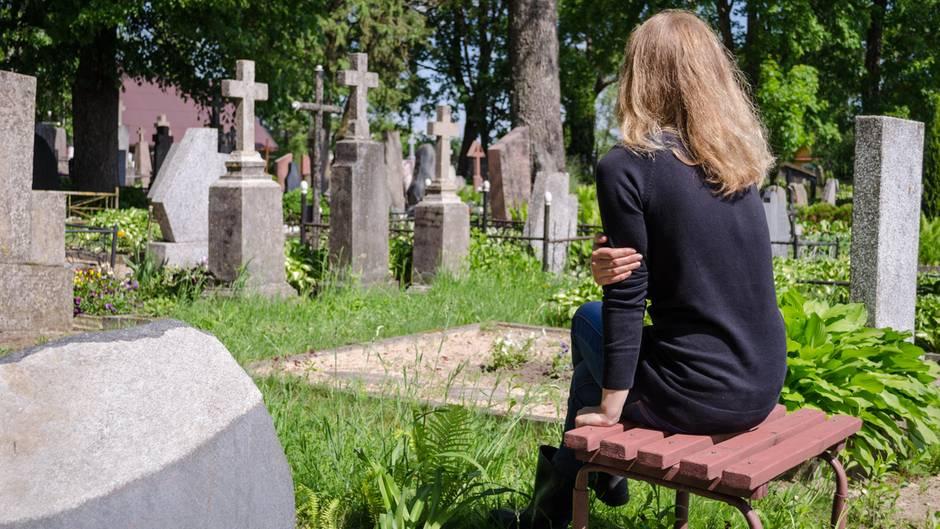 Eine junge Frau sitzt allein vor Grabsteinen