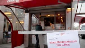 Abstand halten-Schild vor einer Currywurstbude in Berlin