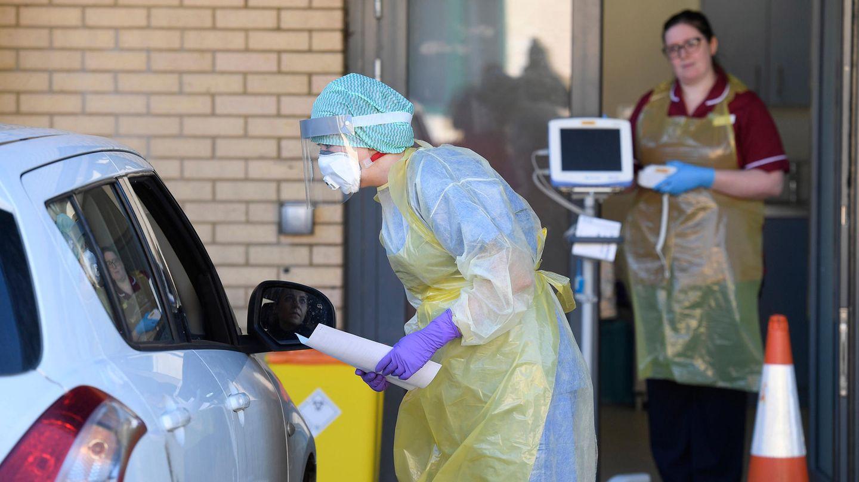 Eine Krankenschwester steht in Schutzkleidung neben einem Auto