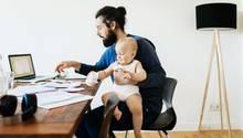 Vater sitzt mit seinem Baby am Computer