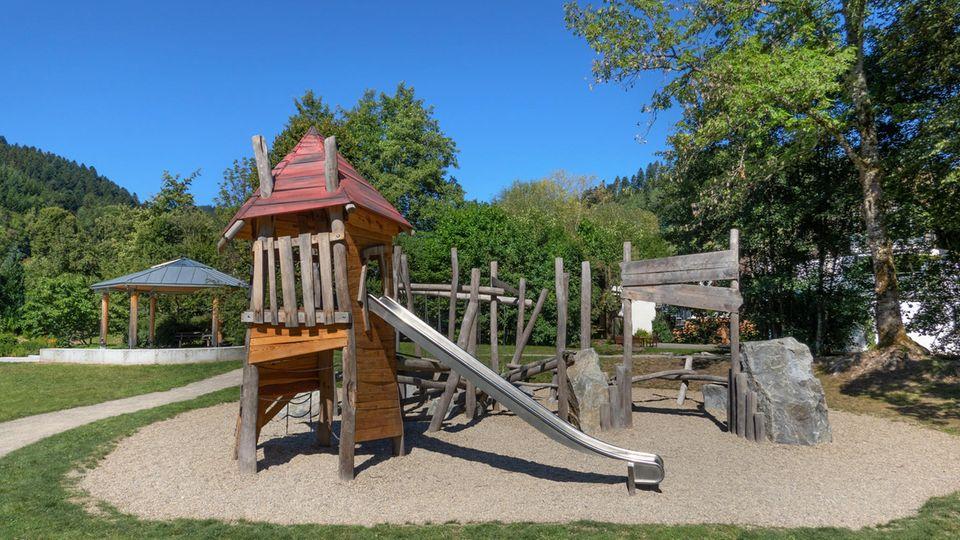 Spielplatz mit Holzhütte und Rutsche